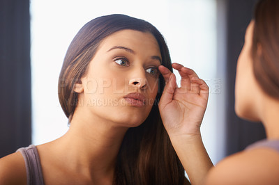 Buy stock photo Shot of a woman looking at her appearance in the mirror