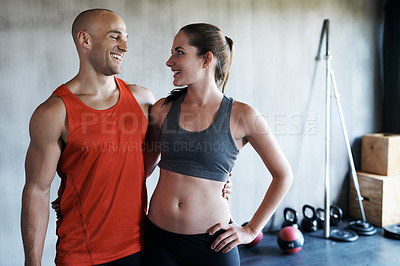Buy stock photo Shot of a young couple training together at the gym