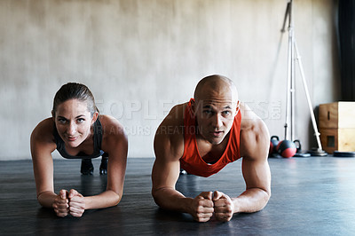 Buy stock photo Shot of a man and woman doing plank exercises at the gym