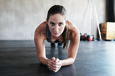 Buy stock photo Shot of a woman doing plank exercises at the gym