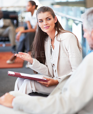 Buy stock photo Attractive young businesswoman assisting a client