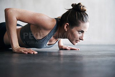 Buy stock photo Shot of a woman doing pushups at the gym