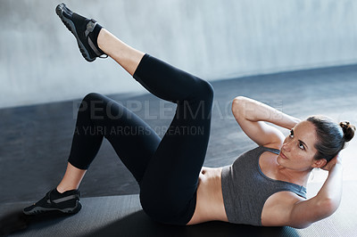 Buy stock photo Shot of a woman doing sit-ups at the gym