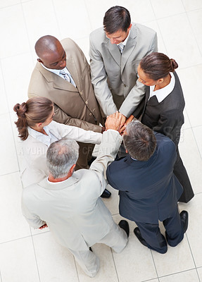 Buy stock photo Upward view of business people standing in a circle with their hands together