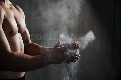 Buy stock photo A cropped view of a male gymnast dusting his hands with chalk