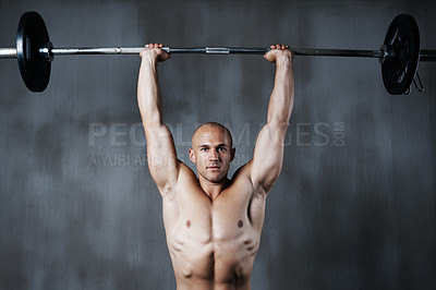 Buy stock photo Shot of a man lifting weights at the gym