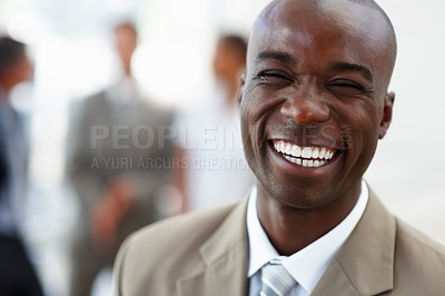 Buy stock photo Portrait of a laughing African American business man with coworkers standing behind