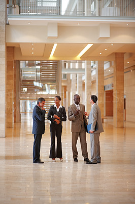 Buy stock photo Portrait of business colleagues standing in a line at a hallway