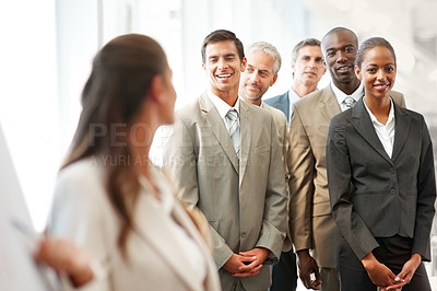 Buy stock photo Group of business colleagues being lectured by a woman at a conference
