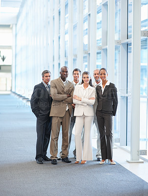 Buy stock photo Portrait of business colleagues standing in a group at a hallway