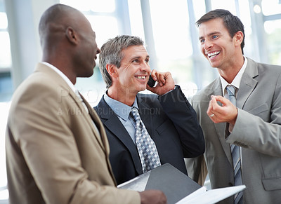 Buy stock photo A handsome business man communicating using mobile with his colleagues standing besides
