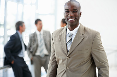 Buy stock photo Portrait of a handsome confident African American business man smiling with his colleagues standing behind
