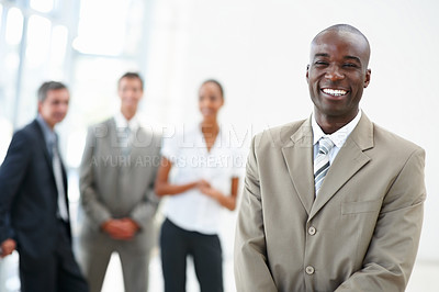 Buy stock photo Portrait of a satisfied young African American business man with coworkers standing behind