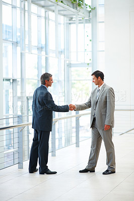 Buy stock photo Full length image of business men shaking their hands at the hallway