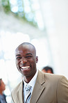 A laughing African American business man with people at the background