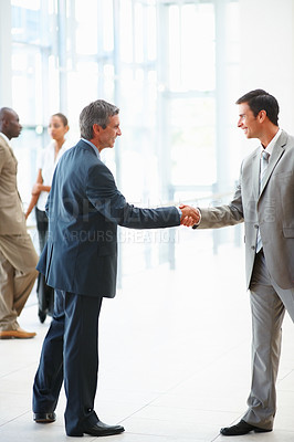 Buy stock photo Two successful business people shaking hands after a business deal