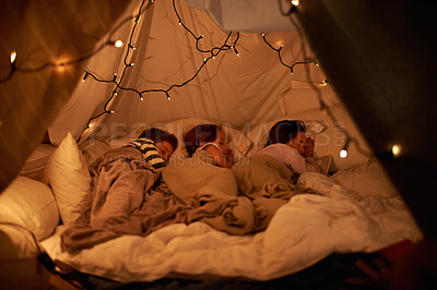 Buy stock photo Shot of three young children sleeping in blanket tent