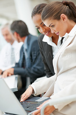 Buy stock photo Teamwork: Young business women working on a laptop