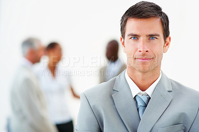 Buy stock photo Portrait of a young business man with colleagues at the background
