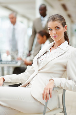 Buy stock photo A beautiful young business woman sitting on the chair with colleagues in the background