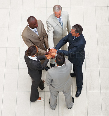 Buy stock photo Upward view of a group of business colleagues with their hands together in unity