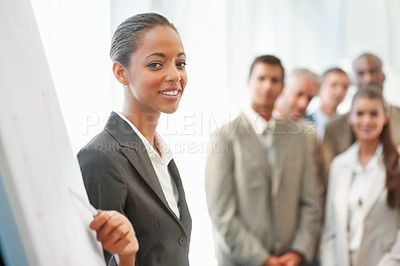 Buy stock photo Cute young business woman lecturing a team of colleagues