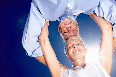 Buy stock photo Upward view of an old couple with their head together with the sky as the background