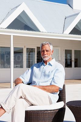 Buy stock photo Portrait of a happy senior man sitting on a designer chair outside his beach house - copyspace