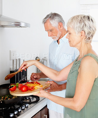 Buy stock photo Portrait of a mature couple preparing food together