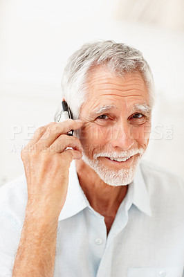Buy stock photo An old cheerful man having fun while talking on mobile phone