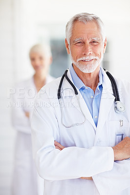Buy stock photo Portrait of a confident senior doctor posing with hands folded
