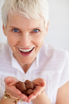 Buy stock photo Senior woman holding chocolates in cupped hands