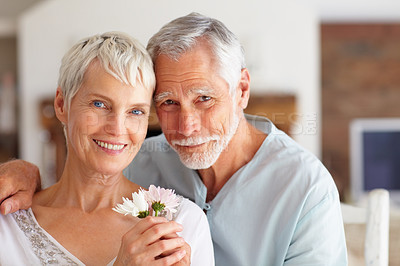 Buy stock photo Portrait of a loving senior couple posing with freshly picked flowers at home - copyspace