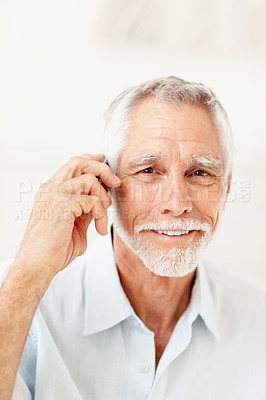 Buy stock photo A handsome old senior man communicating using cellular phone