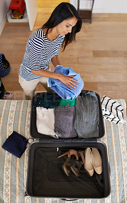 Buy stock photo High angle shot of a woman packing her suitcase