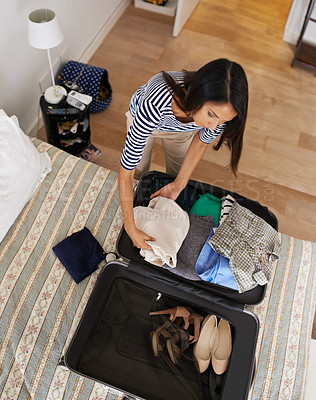 Buy stock photo Shot of a woman packing her clothing in a suitcase