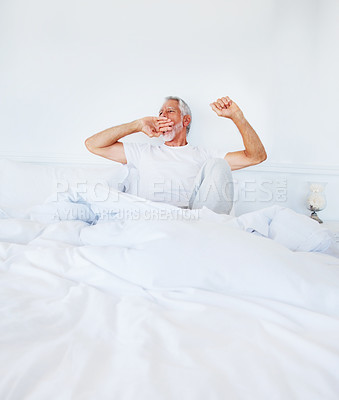 Buy stock photo Image of an old mature man lying on the bed and yawning