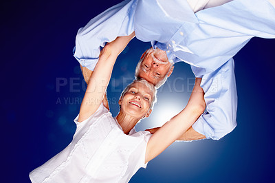 Buy stock photo Upward view of a mature couple with their head together with the sky as the background
