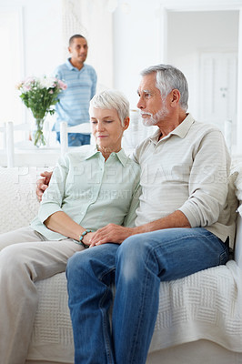 Buy stock photo Portrait of an old couple sitting together with a servant at the back