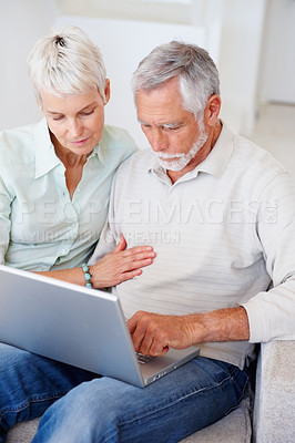 Buy stock photo A senior retired couple sitting and working on a laptop