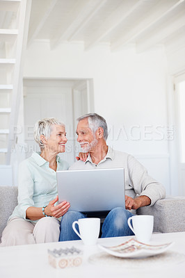 Buy stock photo Happy elderly couple working together on a laptop