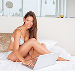 Cute woman in lingerie working on laptop at home
