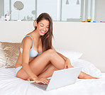 Happy young woman on a bed with laptop