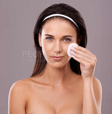 Buy stock photo A young woman wiping her face with cotton wool