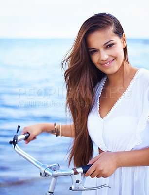 Buy stock photo Cropped shot of a gorgeous tattooed young woman with a bicycle standing beside the sea