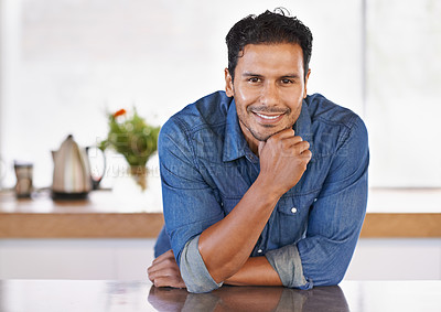 Buy stock photo Portrait of a handsome young man leaning on the kitchen counter at home