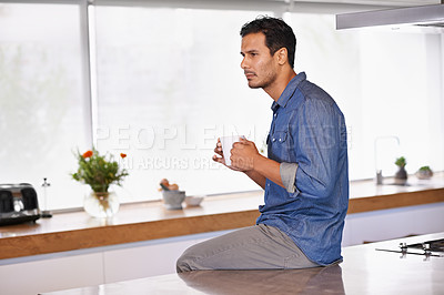 Buy stock photo A serious man holding a mug of coffee and sitting on his kitchen counter