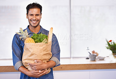 Buy stock photo Portrait of a handsome man holding a shopping bag of healthy food in his arms