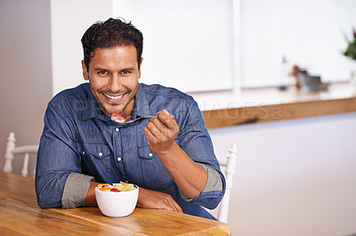 Buy stock photo A portrait of a handsome man eating fruit from a bowl at home