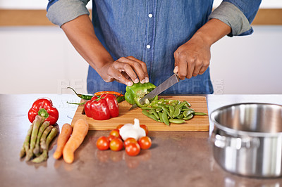 Buy stock photo Cropped view of a man chopping some fresh vegetables on the kitchen counter